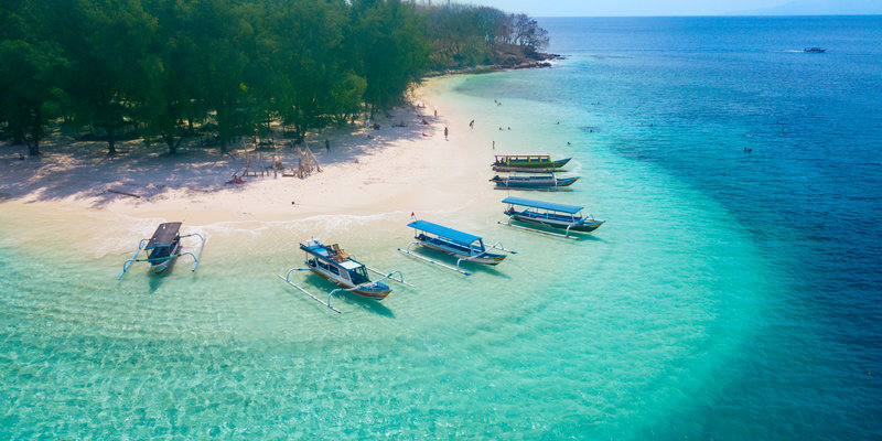 Image of tourist ships anchored on the Gili Rengit beach at Lombok, Indonesia